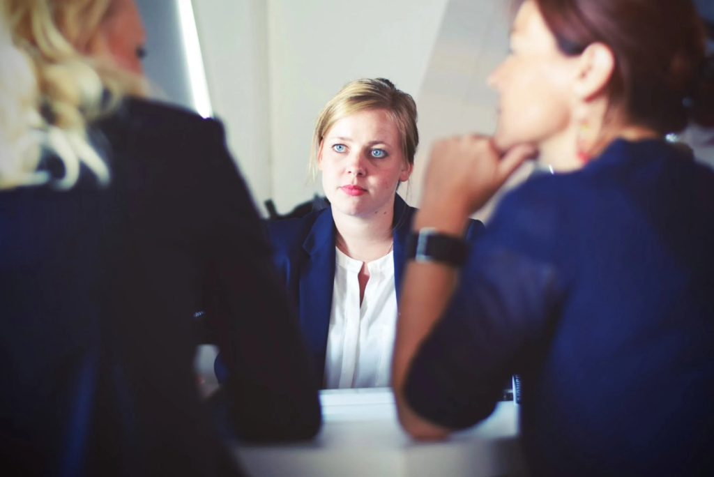 A woman with blonde hair in a navy blue suit sits looking at two women on the other side of a desk as in a meeting
