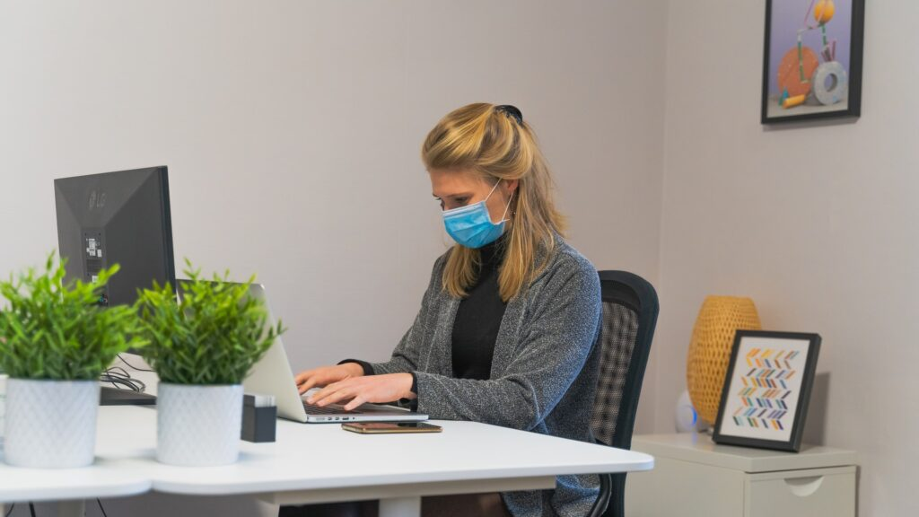 A woman with blonde hair sits behind a white desk. She is typing on a computer keyboard and is wearing a face covering in the form of PPE.