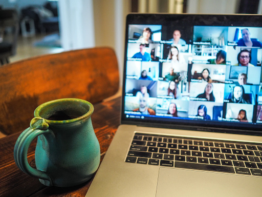 A close up of a laptop screen features a zoom call. There are 20 participants visibile, the others are out of shot. The laptop is balanced on a wooden table and there's a cup of what we can assume is tea or coffee, next to it.